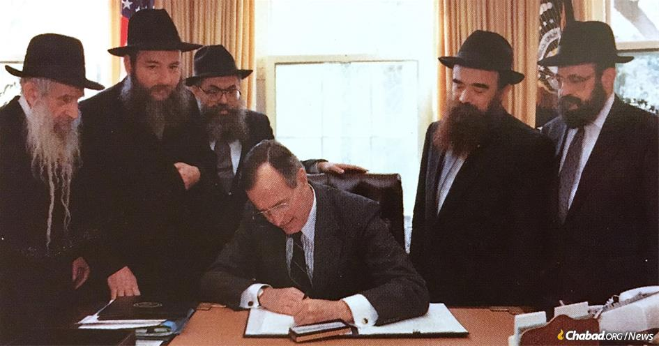 "President George H.W. Bush signing an ""Education Day"" proclamation. Looking on are (from left) Rabbi Menachem Shmuel Dovid Raichik, Rabbi Shlomo Cunin, Rabbi Shimon Lazaroff, Rabbi Abraham Shemtov and Rabbi Moshe Feller."