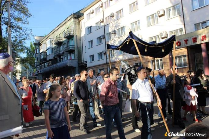 Despite the turmoil, Mariupol has a active Jewish life. Here, a new Torah scroll was welcomed in May.