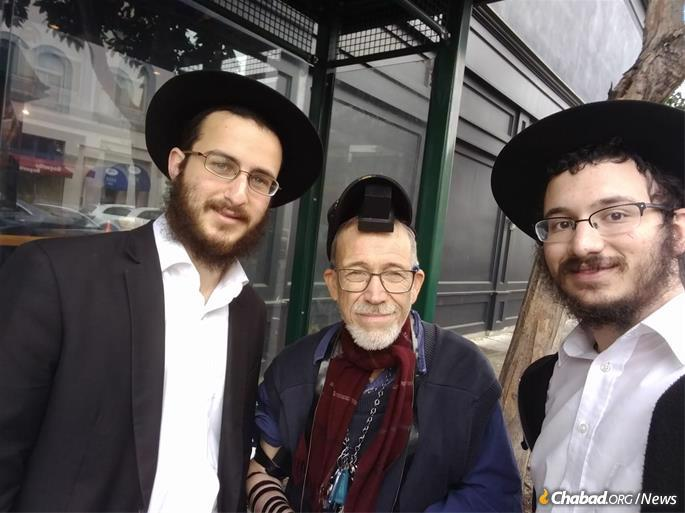 The rabbinical students helped this man put on tefillin for the first time.