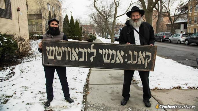 Menachem Posner and Dr. Lubin hold up a Yiddish sign of unknown vintage that once graced a previous location of Anshei Lubavitch. (Photo: Brett Walkow)