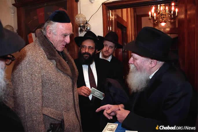"""Federal Judge Jack B. Weinstein, then-chief and today senior judge on the U.S. District Court for the Eastern District of New York, receives a dollar and a blessing from the Rebbe—Rabbi Menachem M. Schneerson, of righteous memory—on Dec. 17, 1989, as Rabbi Sholom Lipskar, founder of the Aleph Institute, looks on. Weinstein was on his way to testify before the Federal Sentencing Commission and told the Rebbe he would be presenting the Rebbe's ideas before them. """"You will support my views also, not just report them?"""" the Rebbe asks, to which Weinstein responded he would. (Photo: Jewish Educational Media/The Living Archive)"""
