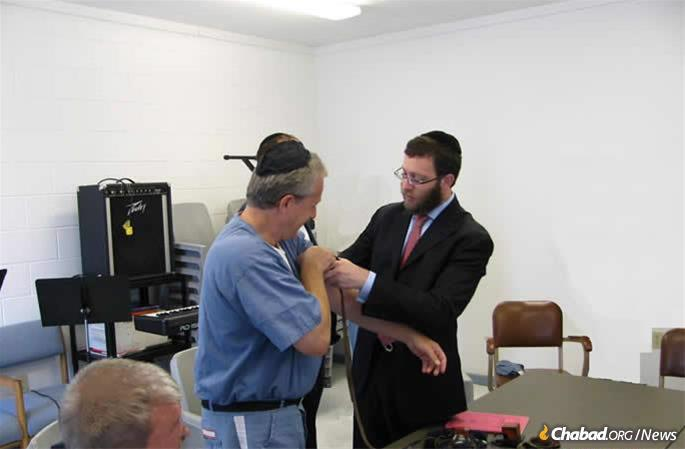Aleph's executive director Rabbi Aaron Lipskar assists an inmate in donning tefillin.