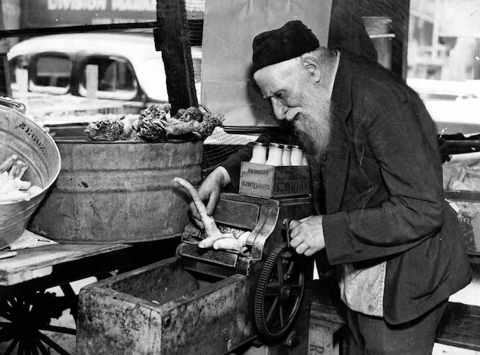 "Maxwell Street featured a mix of small-time vendors and peddlers. This man eked out a living by grinding horseradish (""chrein"") by hand. (Chicago Tribune Historical Photo)"