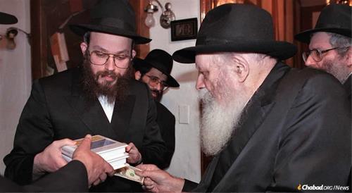 O rabino Yonah Avtzon presenteia o Rebe com dois volumes publicados por Sichos em inglês e recebe um dólar e uma bênção em 23 de fevereiro de 1992 (19 de abril de 5752). (Foto: JEM)