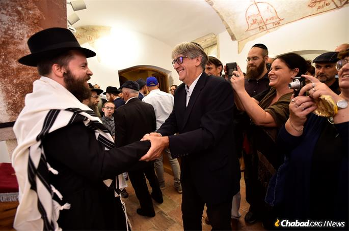 Faith greets dignitaries who came to celebrate his installation as rabbi of the ancient synagogue.