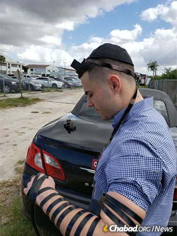 Hunter Pollack, whose sister, Meadow Pollack, was killed in the shooting, dons tefillin before the memorial service.