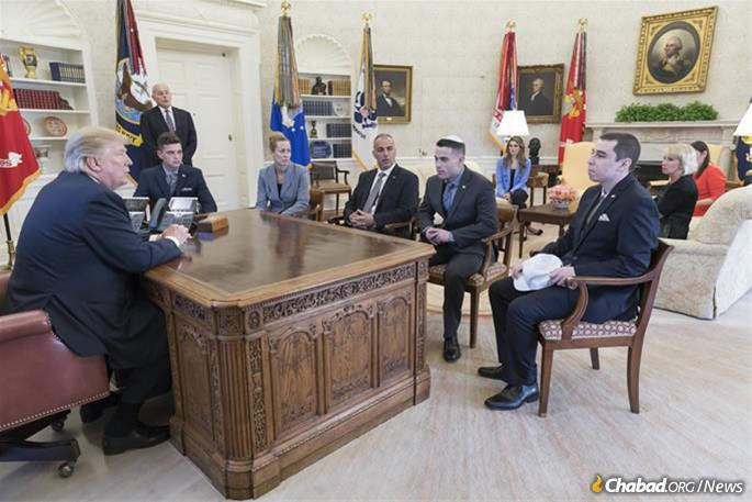 """Meadow Pollack's family meeting with President Donald Trump, left, at the White House last year. Her brother, Hunter, says he wore a kippah to send a message that his peers should """"be proud to be Jewish."""" From left, around the desk: Brandon Schoengrund, Julie Phillips-Pollack, Andrew Pollack, Hunter Pollack and Huck Pollack. Standing by the door is White House Chief of Staff John Kelly. (Official White House Photo by Shealah Craighead)"""