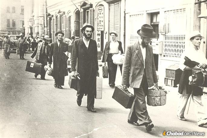 Avraham Tzvi Landa, center with umbrella, arrives in Kobe, Japan, with fellow yeshivah students.