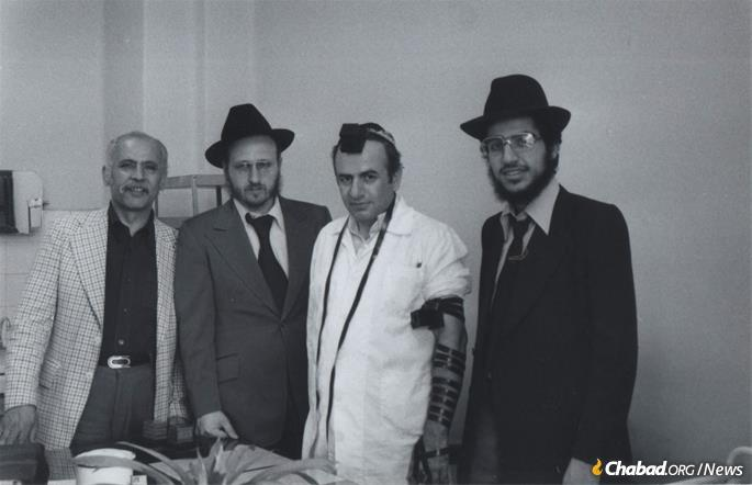 Hecht, second from left, and Illulian, far right, help an Iranian Jew don tefillin. (Photo: Courtesy NCFJE)