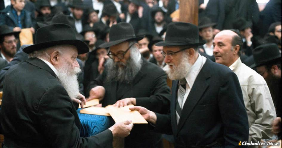 Rabbi Avraham Tzvi Landa receives a Chassidic discourse and a blessing from the Lubavitcher Rebbe in 5750 (1989). (Photo:JEM)
