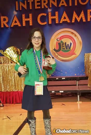 """Leah Ada Klein, 9, winner of the JewQ contest in the fourth-grade division, holds a trophy she described as """"big as two rulers."""" She represented Chabad of Niagara Falls in Canada."""