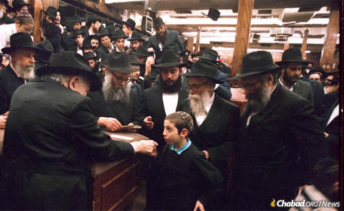Reb Velvel waiting to receive a dollar from the Rebbe in the winter of 1991. (Photo: JEM)