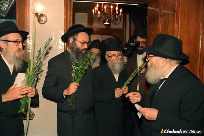 "The Rebbe handing Reb Velvel a set of ""hadassim"" (myrtle branches) prior to Sukkot 5748 (1987). (Photo: JEM)"