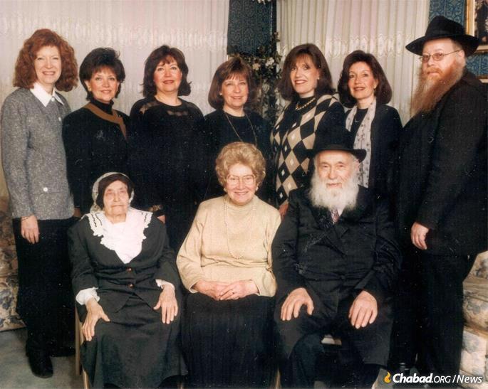 Shula Kazen sentada entre sua mãe e marido, com seus sete filhos.