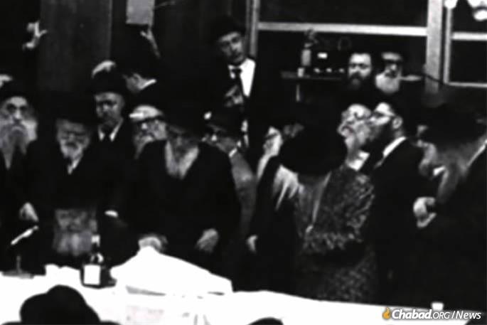 """O Skulener Rebe, em frente, o segundo da direita, permanece como o Lubavitcher Rebe, sentado à esquerda, oferece um """"maamar"""" (discurso) chassídico."""
