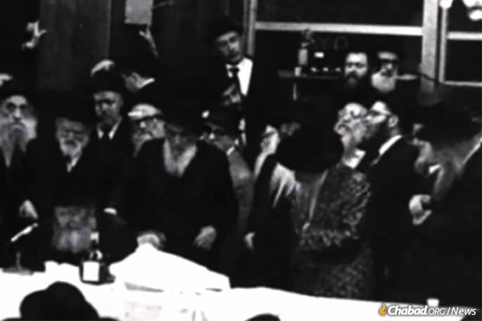 """The Skulener Rebbe, front, second from right, stands as the Lubavitcher Rebbe, seated left, delivers a Chassidic """"maamar"""" (discourse)."""