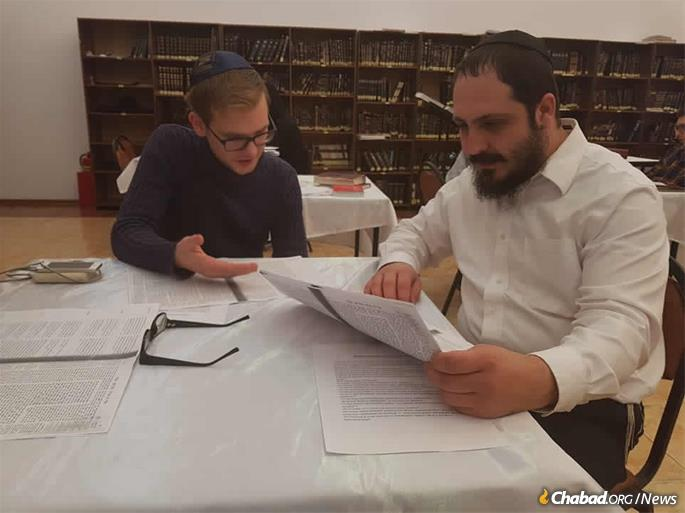 The rabbi studies Talmud with a local young adult.
