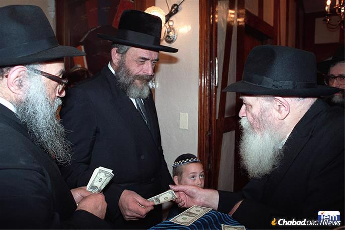 Rabbi Landa receives a dollar and a blessing from the Rebbe. (Photo: JEM)