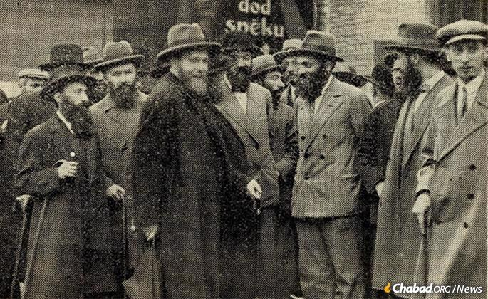 Rabbi Yosef Yitzchak (center, holding a cane, partially obscured) at the Riga train station circa 1930, speaking to Mordechai Dubin (in bowler hat with bowtie). The Rebbe's eldest son-in-law, Rabbi Shmaryahu Gourarie, is at center-left. (Photo: Rabbi Mordechai Glazman via Jewish Educational Media/Early Years)