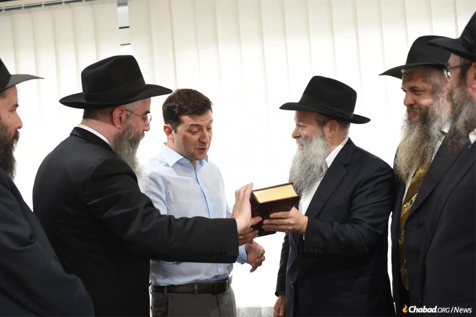 President-elect Volodymyr Zelensky, Ukraine's first-ever Jewish president, held a high-profile meeting with Ukraine's regional chief rabbis on May 6. Here, the comedian-turned-politician is presented with a Chumash in Russian translation by Rabbi Shmuel Kaminezki and Rabbi Avraham Wolff, as other members of the delegation look on.