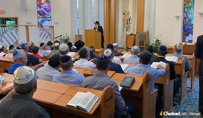 Rabbi Yisroel Goldstein, who was shot and wounded at the Chabad of Poway synagogue a week earlier, addresses the congregation prior to the onset of the following Shabbat, when hundreds turned out for services and a communal dinner.