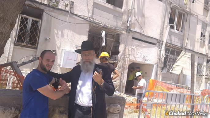 Local Chabad-Lubavitch emissaries, including Rabbi Menachem Mendel Gurelik, above, took to the streets to put tefillin on men during bomb-shelter breaks in a gesture of spiritual and protective support.