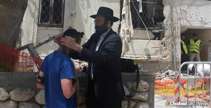 Rabbi Moshe Vilenkin assists a local resident with tefillin.