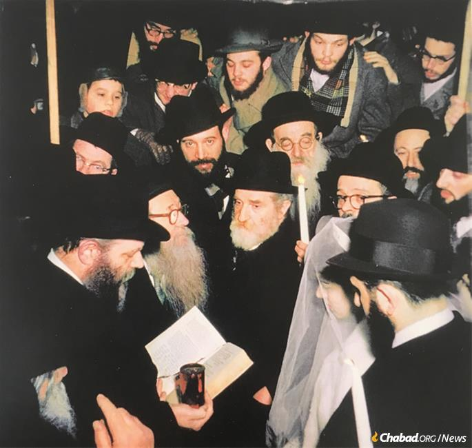 "In a private audience with the Rebbe, Raskin asked him to officiate at his wedding. The Rebbe, who had requested of Raskin that he grow a beard, replied: ""If you do what I ask of you, I'll do what you ask of me."" Raskin agreed. The Rebbe (on left, holding wine) officiating on Feb. 9, 1959."