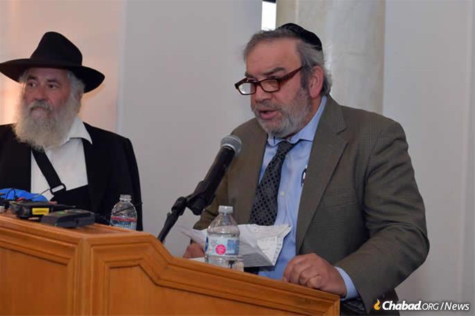 Dr. Howard Kaye speaks at the memorial as Rabbi Yisroel Goldstein looks on.