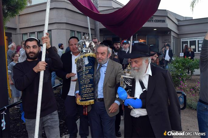 After the final letters in the scroll were written, Dr. Howard Kaye and Rabbi Yisroel Goldstein led a parade through the streets carrying the finished Torah.