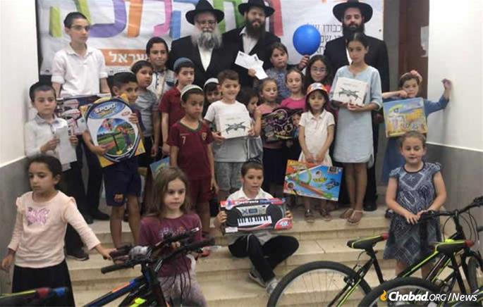 L to R: Rabbi Moshe Zeev Pizam, Rabbi Chananel Pizam, and Rabbi Asher Pizam with children who received gifts after an attack to lift their spirits.