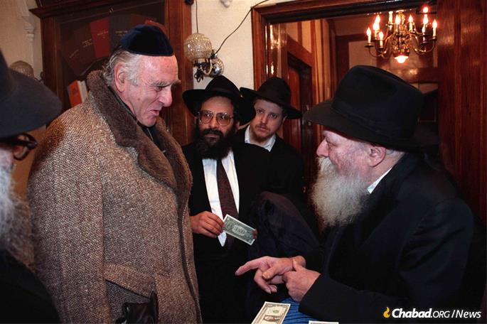 Judge Jack B. Weinstein, then-chief and today senior judge on the U.S. District Court for the Eastern District of New York, receives a dollar and a blessing from the Rebbe—Rabbi Menachem M. Schneerson, of righteous memory—on Dec. 17, 1989, as Rabbi Sholom Lipskar, founder of the Aleph Institute, looks on. Weinstein was on his way to testify before the Federal Sentencing Commission. (Photo: Jewish Educational Media/The Living Archive.)