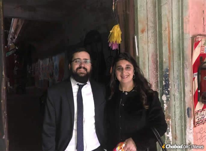 Rabbi Shneur Mizrahi and his mother with the new mezuzah, which was affixed to the building.
