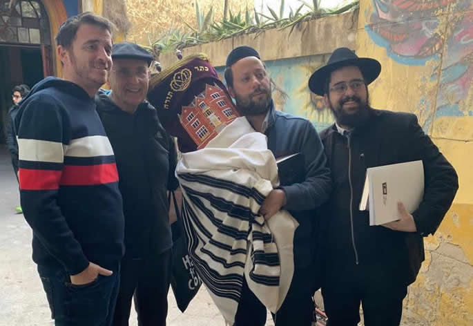 Rabbi Shneur Mizrahi, right, and community members return a Torah scroll to the synagogue.