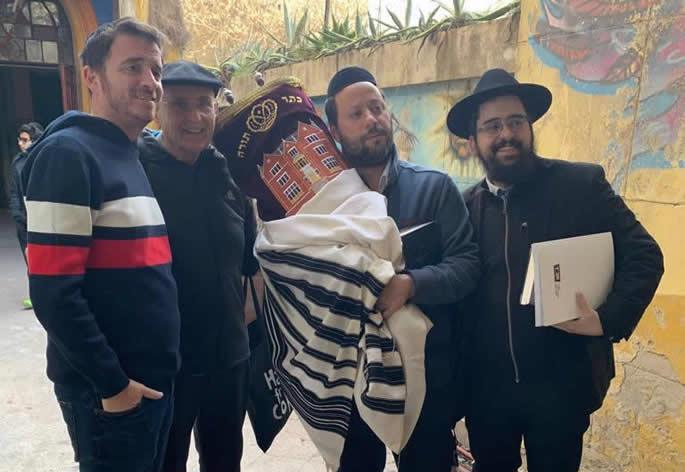Rabbi Shneur Mizrahi, right, and community members return a Torah scroll to the synagogue.