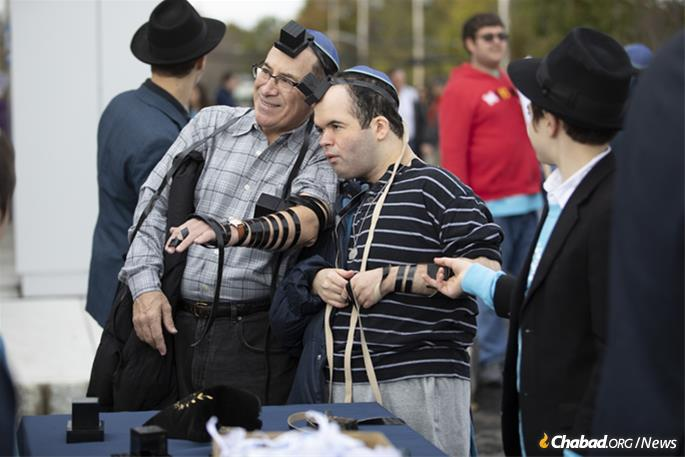 """""""Every soul has a unique personal mission to fulfill in this world,"""" says Rabbi Zalman Grossbaum. Above, Keith Lerner puts on tefillin with his son, Max. (Photo: Mendel Grossbaum)"""
