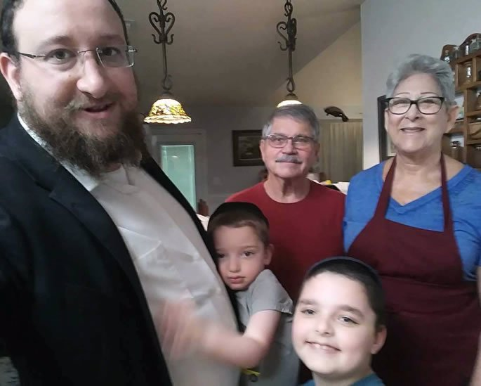 The author in her kitchen with with her husband, Lee, and Rabbi Yosef Goldwasser with sons Mendel and Berel.