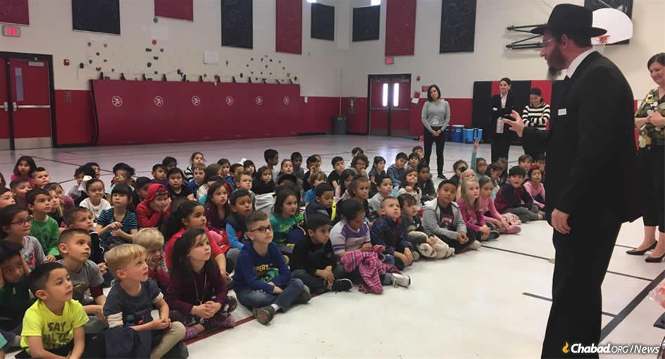 Rabbi Levi Greenberg talks to El Paso public-school children about the importance of giving charity and doing acts of kindness.