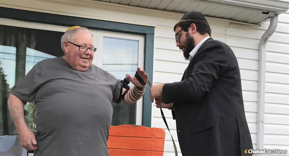Rabbi Mendel Super helps Bob Friedman of North Battleford, Saskatchewan, Canada, put on tefillin.