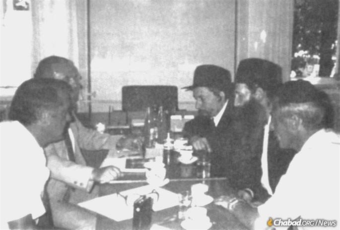 Rabbi Yitzchak Kogan and Rabbi Sholom Ber Levine (second and third from right, respectively) meet with KGB officials in Kiev on Aug. 7, 1991.