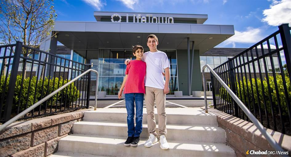 The $18 million LifeTown center celebrates its grand opening on Sept. 9 in Livingston, N.J. A project of Friendship Circle of New Jersey, the center is built on young people volunteering to assist children with special needs, like Eitan Shua, left, and Kyle Fink. (Photo: Mendel Grossbaum)