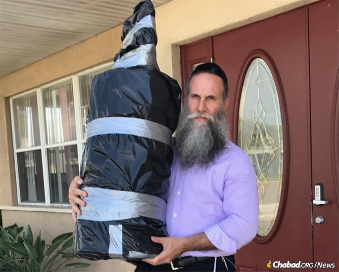 Rabbi Zvi Konikov with one of three Torah scrolls being transported off Satellite Beach, the barrier beach where Chabad of the Space & Treasure Coasts is located, and onto the Florida mainland for safekeeping.