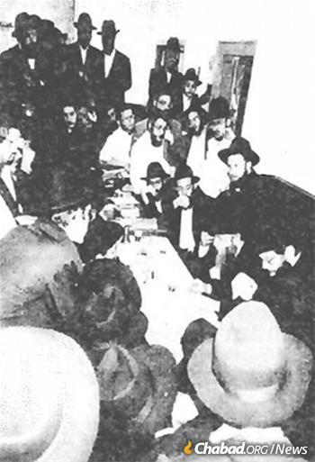 Rabbi Shlomo Cunin and Rabbi Yosef Aharonov lead a farbrengen with yeshivah students in New York following their historic August 1991 private audience with the Rebbe.