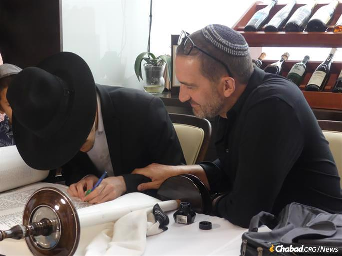 Rabbi Shimon Shimonov of Vienna, Austria, oversaw the final filling in of letters on the scroll. To his right is Bratislava Jewish Community president Dr. Tomas Stern.