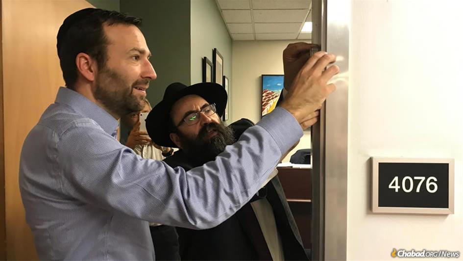 "California State Sen. Ben Allen, author of the state's landmark ""Mezuzah Bill,"" and Rabbi Mendy Cohen of Chabad of Sacramento, Calif., affix a mezuzah on Allen's office door following passage of the legislation. (Photo: Legislative Jewish Caucus)"