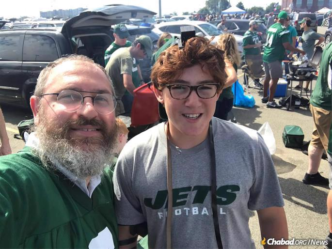 "Armed with tefillin and a shofar, Rabbi Eli Goodman led a group of congregants at the Jets opening day in what is being dubbed the ""Tefillin Tailgate."" This young man put on tefillin for the first time."