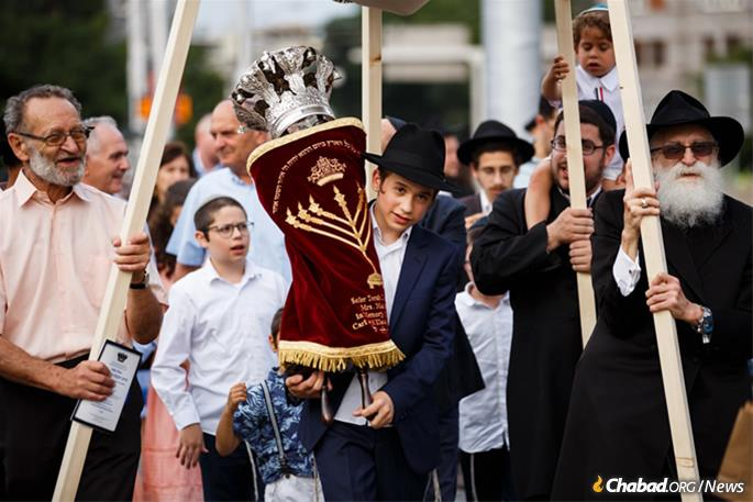 As part of a joyous dual event, the bar mitzvah boy, Tzali Myers, center, carried the Torah scroll and helped lead the customary celebratory procession.