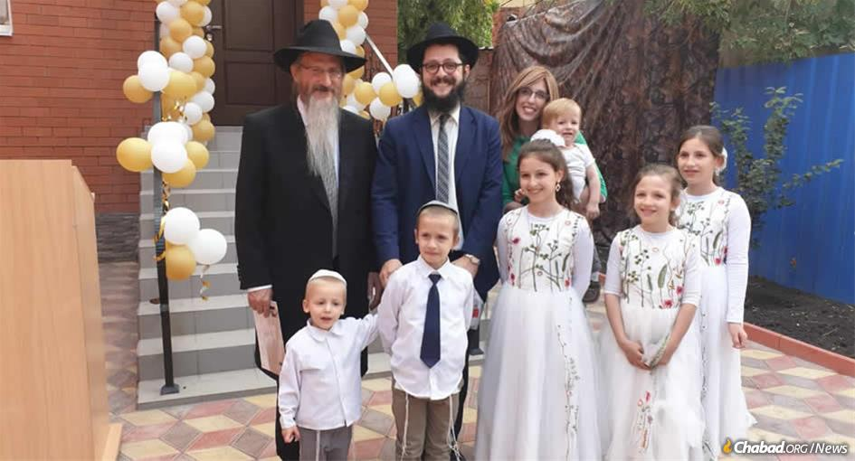 Chief Rabbi of Russia Berel Lazar, left, with Rabbi Yisroel and Deborah Melamed, and their children, in front of the new mikvah in Astrakhan, Russia.