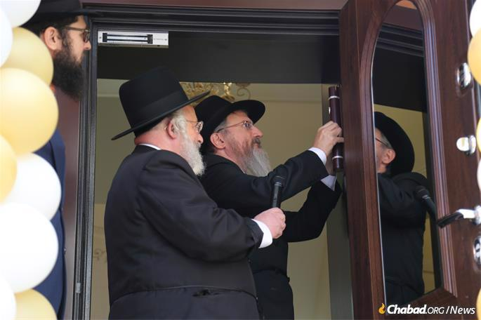 Lazar affixes the mezuzah, as others look on.