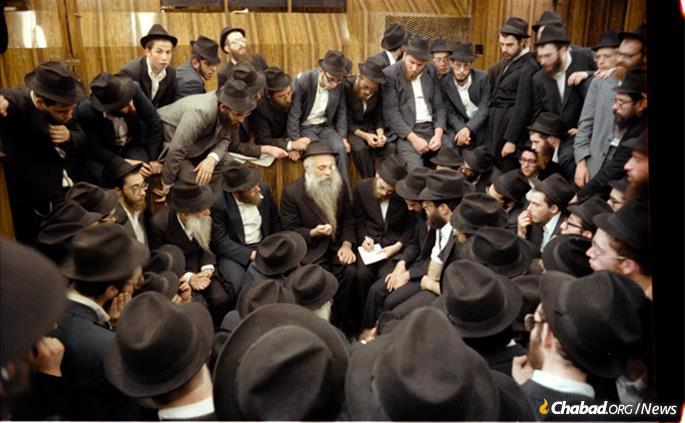 Chazarah, or repetition, following the Rebbe's farbrengen on Sept. 23, 1979. Rabbi Yoel Kahan is in the center, elucidating a point, while to his right, taking notes, is Rabbi Dovid Feldman, today chief editor of Lahak, which rendered the Rebbe's talks into Hebrew. Chazzarah took place in the synagogue and was open to everyone. (Photo: Jewish Educational Media/The Living Archive)